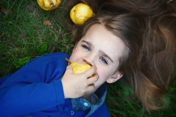 Little girl lying on the grass eating fruits