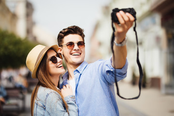Happy couple of tourists taking from camera selfie in old city