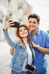 Happy tourists taking selfie on city street. Couple have great summer vocation in new destination