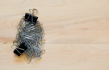 a small pile of silver paper clips with 2 black binder clips on a wooden desk with copy space