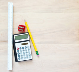 back to school or office-a yellow pencil, a red pencil sharpener, a small calculator and a white triangular ruler on a wooden desk with copy space