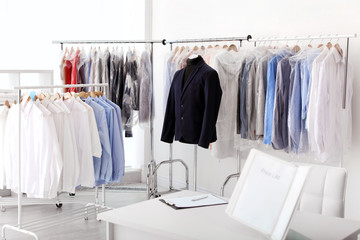 Dry-cleaner's interior with clothes on racks
