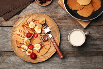 Delicious pancakes with strawberry, banana and syrup served for breakfast on table