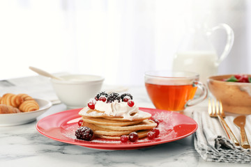 Delicious pancakes with berries and cream served for breakfast on table