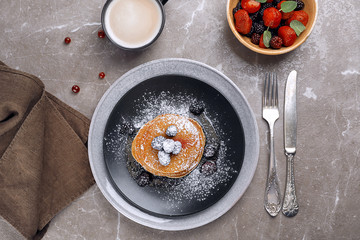 Delicious pancakes with berries and powdered sugar served for breakfast on table