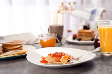 Delicious pancakes with jam served for breakfast on table
