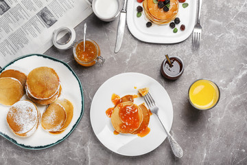 Delicious pancakes with jam and glass of juice served for breakfast on table