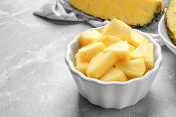 Bowl with fresh sliced pineapple on table