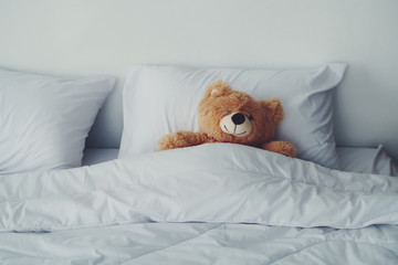 A bear doll laying on white bed.