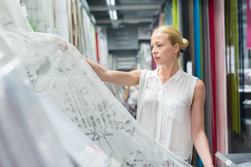 Beautiful young caucasian woman buying white curtains for her apartment in modern home decor furnishings store. Shopping in retail store.