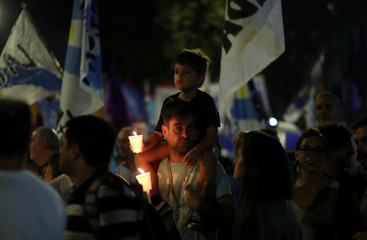A man and a boy hold candles during a protest against an increase in utilities prices in Buenos Aires