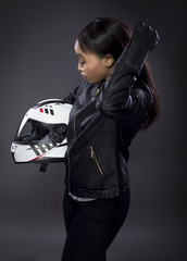 Black female motorcycle rider or race car driver wearing a racing helmet and leather jacket. Part of the gritty woman series, a competitive biker or racer getting ready for competition.