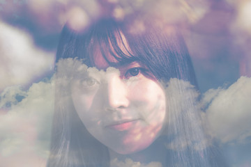 Double exposure, Portrait of young beautiful woman in spring garden and blue sky background.