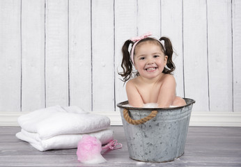 Cute little girl in  pink headband sits in bubble bath in tiny, metal wash tub