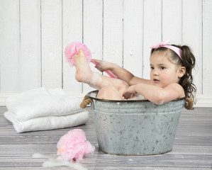 Toddler girl lost in thought while scrubbing toes in tiny metal bathtub