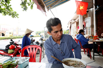 Vietnamese deportee and Amerasian Pham Chi Cuong, 47, who was deported from U.S., eats along a street in central Ho Chi Minh City