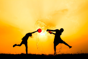 Silhouette of children playing water during sky sunset, Songkran Festival in Thailand and summer season