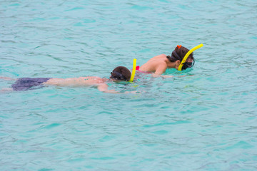 Beach vacation couple wearing a snorkel scuba mask making a goofy face while swimming in ocean water. Closeup portrait of boy on his travel holidays. Summer or winter destination.