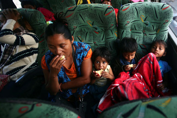 Central American migrants from Guatemala, moving in a caravan through Mexico, eat as they travel to Mazatlan as part of their new travel route, in Tlaquepaque