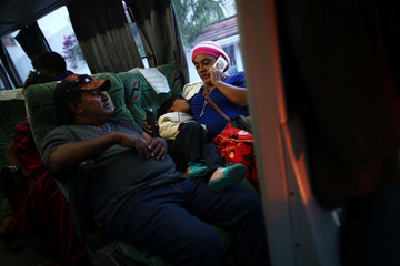 A Central American migrant, moving in a caravan through Mexico, smiles as she travels to Mazatlan as part of her new travel route, in Tlaquepaque