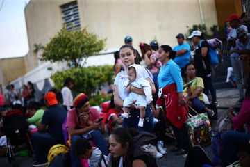 A Central American migrant, moving in a caravan through Mexico, holds a baby as she waits for a bus to Mazatlan as part of her new travel route, in Tlaquepaque