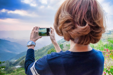 Tourist woman shooting photography by smartphone at landscape view mountain and cloudy sky.