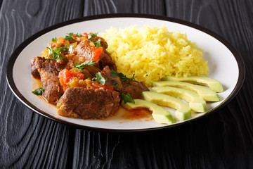 Ecuadorian traditional food: seco de chivo goat meat with a garnish of yellow rice and avocado close-up. horizontal