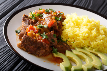 Ecuadorian seco de chivo goat meat with a garnish of yellow rice and avocado close-up. horizontal