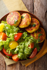 Delicious hot potato pancakes with fresh vegetable salad close-up. Vertical top view