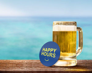 Happy Hour Concept for Bar, Cafe or Hotel Resort to Promote a Special Offer to Customer. Glass of Beer on Wooden Table with Smiley Face and Text on Note. Relaxation on the Seaside