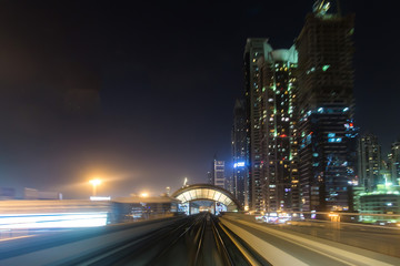 Front cabin view from modern driver-less metro train rush forward, along night Dubai smooth timelapse. Overground railway, dark low rise buildings around, bright road lights at night.