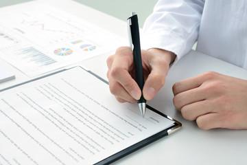 契約書にサインする女性の手