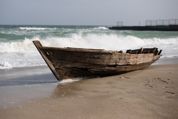 large waves cover a small old boat