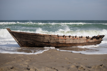 the old boat stands on the seashore during a storm