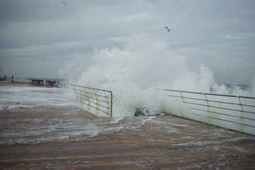 huge waves cover the pier during a storm