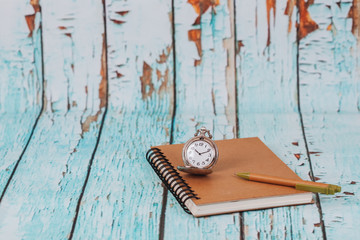 Vintage pocket watch on book note.