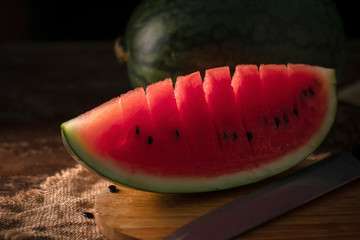 watermelon and watermelon pieces in a wooden background