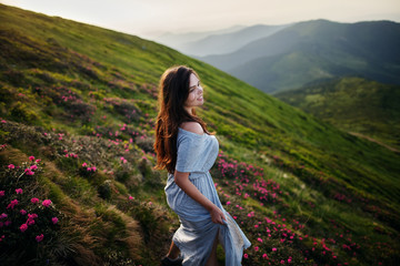 Beautiful woman in dress running in the mountains. Beautiful girl looking happy and smiling. Relaxing, feeling alive, breathing fresh air, got freedom from work. Flowers in the mountains