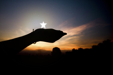 silhouette of hand asking and holding star