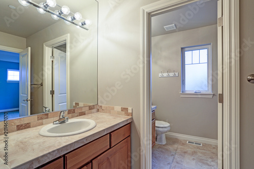 narrow home laundry with white cabinets and red appliances stock rh fotolia com White Laundry Room Doors White Cabinets above Washer and Dryer