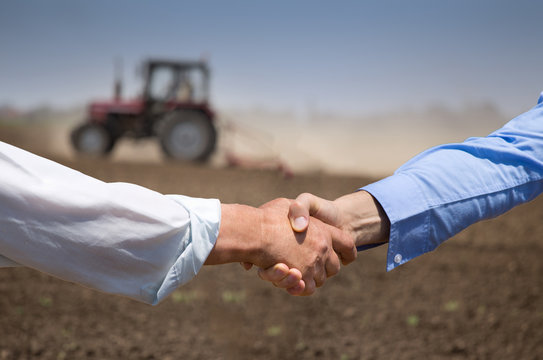 Farmers shking hands in front of tractor