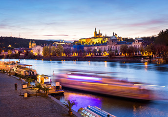 Boat on the Vltava at night with St. Vitus Cathedral in the background, Prague