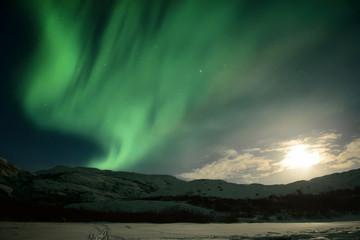 Night winter landscape with Moon and aurora borealis on the sky. Barents sea coastline, Kola peninsula, Russia.