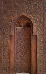 Fatimid era style wooden sculpted mihrab (niche) in wooden wall decorated with floral and geometric patterns, Cairo, Egypt