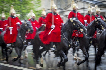 Royal guards on horseback dressed in ceremonial red coats pass with motion blur in a parade on a rainy day in London, England, UK. Shot with slow shutter speed.