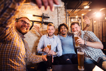Happy mixed-race male friends taking a selfie while sitting at the local bar with draft beer.