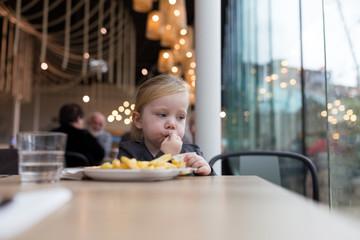 Girl eating fries in restaurant