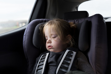 Tired little girl sleeping in the back of the car