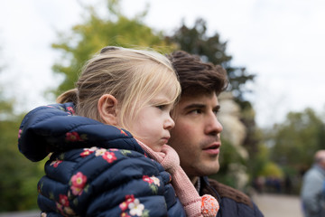 Father holding daughter on shoulder to look at something