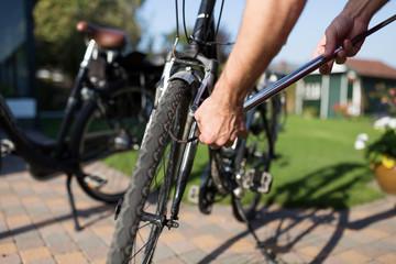Man pumping up tyres of bike